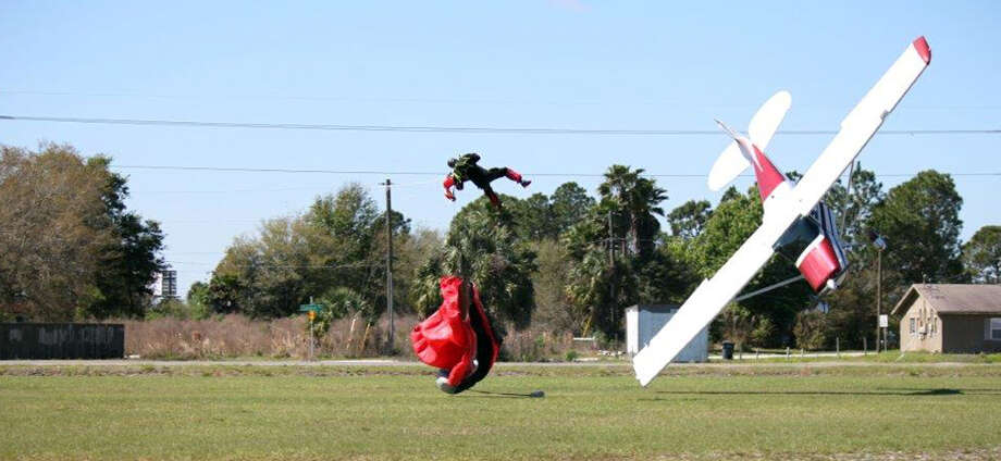 This photo released by the Polk County Sheriff's Office shows a plane nose-diving into the ground after getting tangled with a parachutist, left, Saturday March 8, 2014, at the South Lakeland Airport in Mulberry, Fla. Both the pilot and jumper hospitalized with minor injuries. (AP Photo/Polk County Sheriff's Office, Tim Telford)  Photo: Tim Telford, AP / AP2014