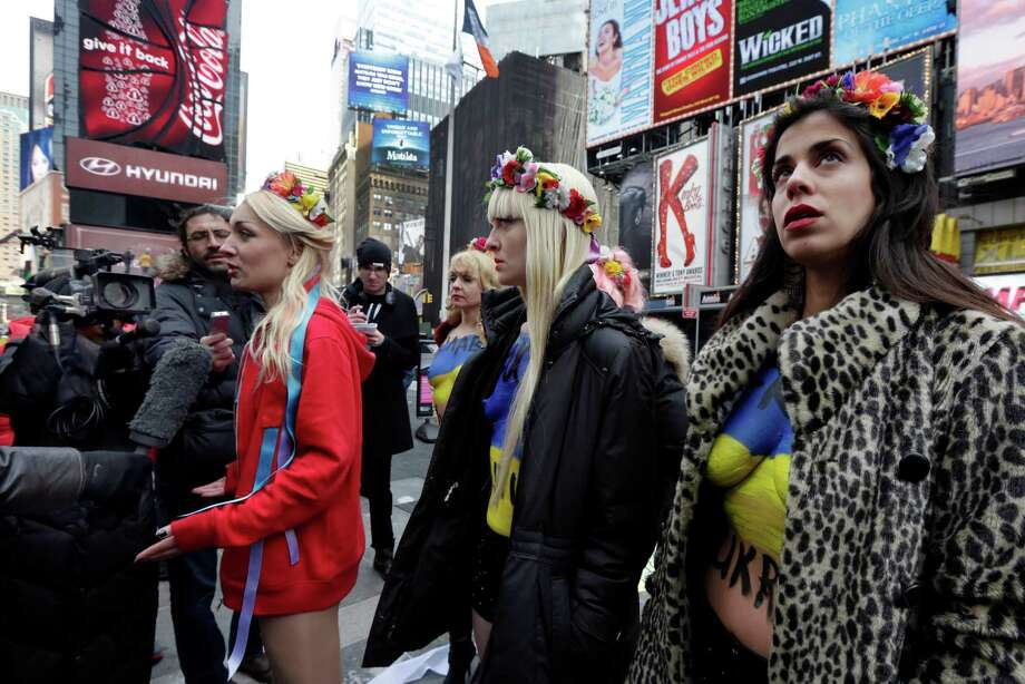 Female activist members of FEMEN are interviewed after during their anti-Putin, pro-Ukraine demonstration in New York's Times Square, Thursday, March 6, 2014. Photo: Richard Drew, AP / AP