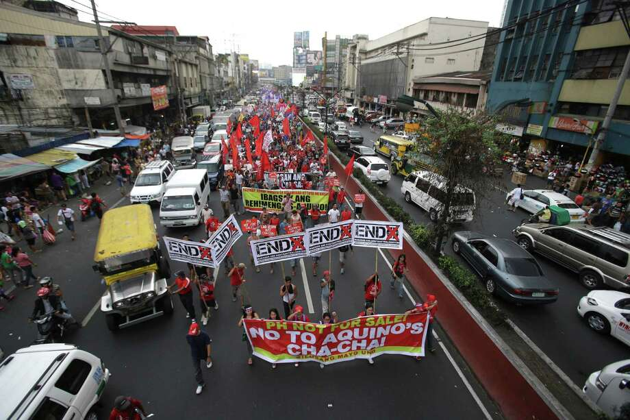Women activists march towards the Malacanang Palace to mark International Women's Day in Manila, Philippines on Saturday, March 8, 2014. The group are blaming Philippine President Benigno Aquino III who they alleged to have neglected women and their families. Photo: Aaron Favila, AP / AP