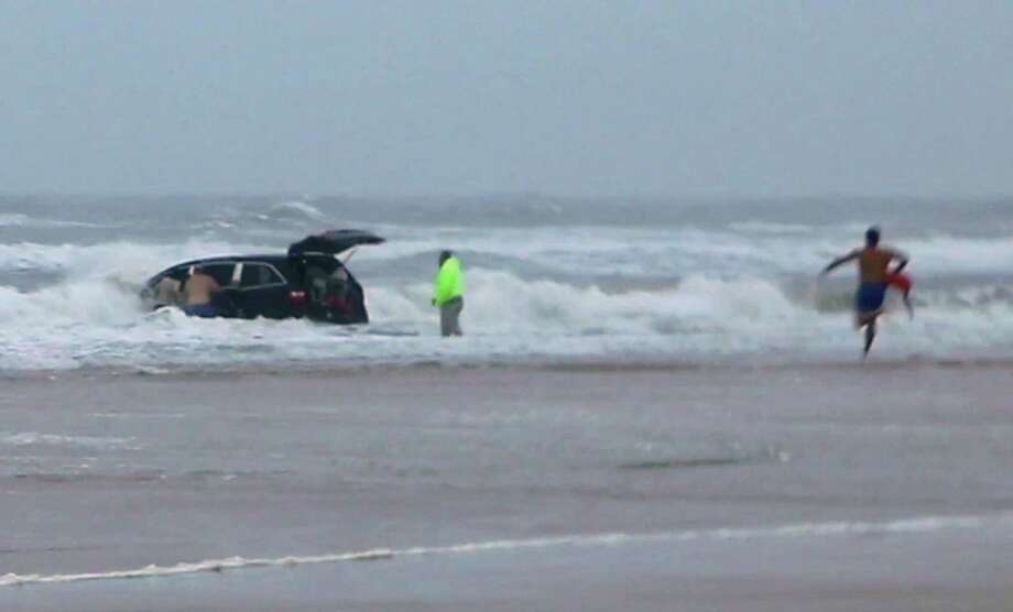 In this image made from video, lifeguards and bystanders rescue children from a minivan that their mother, 31-year-old Ebony Wilkerson, drove into the Atlantic, Tuesday, March 4, 2014 in Daytona Beach, Fla. The pregnant South Carolina woman who drove the minivan carrying her three young children into the ocean surf had talked about demons before leaving the house, according to her sister who worriedly called police, officials said during a news conference Wednesday. (AP Photo/Simon Besner)  Photo: Simon Besner, AP / Simon Besner