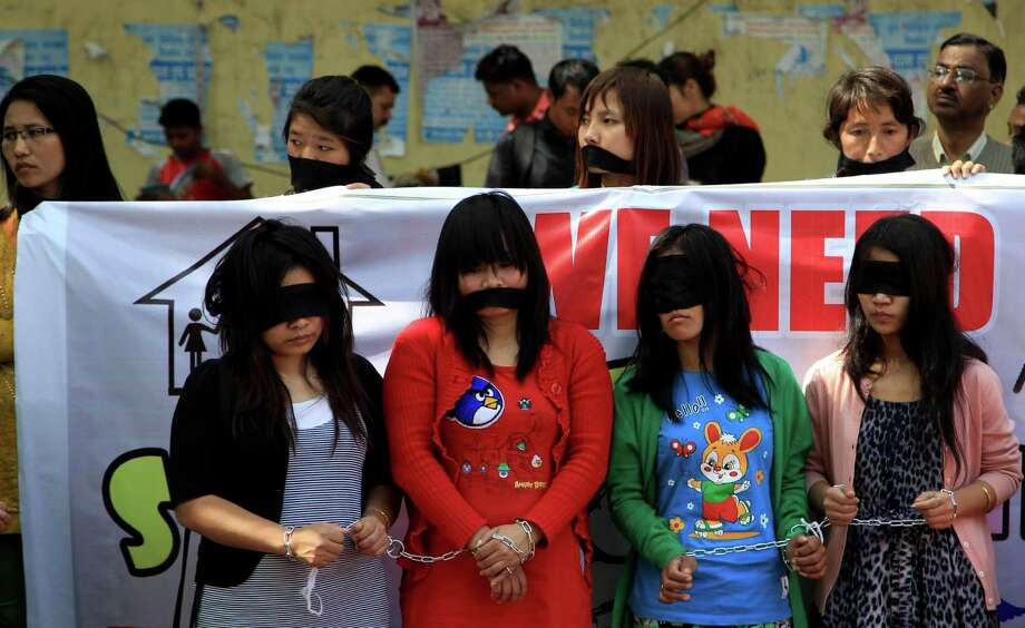 Myanmarese refugee women handcuff, blindfold and cover their mouths with black cloths during a protest on International Women's Day in New Delhi, India Saturday, March 8, 2014. Myanmarese in Delhi alleged their government used forms of violence against women as weapons of war and demanded an end to it. They also urged India for protection from sexual violence, healthcare and education for their children in India. Photo: Tsering Topgyal, AP / AP2014