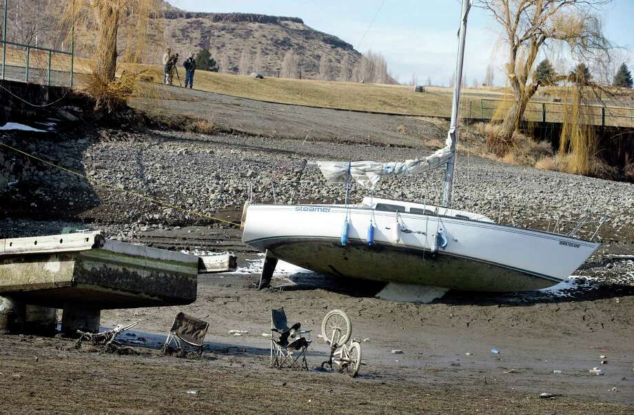 A sailboat owned by Bryan Stockdale, of Vantage, Wash., is left in the mud at the Vantage Riverstone Resort dock in Vantage on Monday, March 3, 2014, as up to 20 feet of water is let out of the Columbia River reservoir behind Wanapum Dam after a spillway pillar was discovered to be cracked at the dam last week. Garbage is seen that had been left in the water at the end of the dock. Photo: Don Seabrook, AP / The Wenatchee World