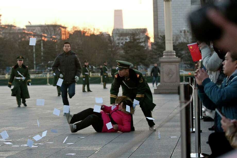 A petitioner is pushed on the ground by a paramilitary policeman after she ran into a cordoned off area near a national flag pole on Tiananmen Square and threw up flyers to protest her case of injustice during a national flag raising ceremony early in the morning before the opening session of the annual National People's Congress at the nearby Great Hall of the People in Beijing, China, Wednesday, March 5, 2014. Photo: Alexander F. Yuan, AP / AP