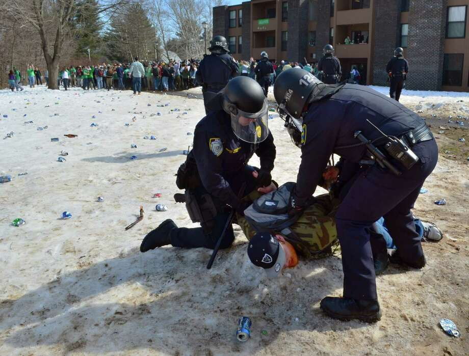 "Police detain a participant in the pre-St. Patrick's Day ""Blarney Blowout"" near the University of Massachusetts in Amherst, Mass. on Saturday, March 8, 2014.  Amherst police said early Sunday that 73 people had been arrested after authorities spent most of the day Saturday attempting to disperse several large gathering around the UMass campus for the party traditionally held the Saturday before spring break. The partying carried through Saturday evening into early Sunday, and Amherst Police Capt. Jennifer Gundersen said in a statement that police were busy with numerous reports of fights, noise and highly intoxicated individuals. (AP Photo/The Republican, Robert Rizzuto)  Photo: Robert Rizzuto, AP / The Republican"