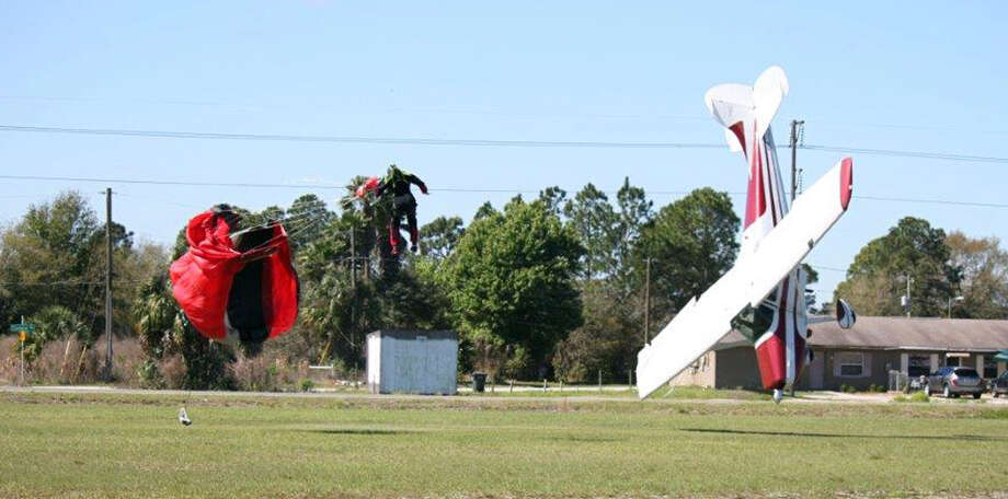 This photo released by the Polk County Sheriff's Office shows a plane nose-diving into the ground after getting tangled with a parachutist, left, Saturday March 8, 2014, at the South Lakeland Airport in Mulberry, Fla. Both the pilot and jumper hospitalized with minor injuries. (AP Photo/Polk County Sheriff's Office, Tim Telford)  Photo: Tim Telford, AP / THE ASSOCIATED PRESS2014