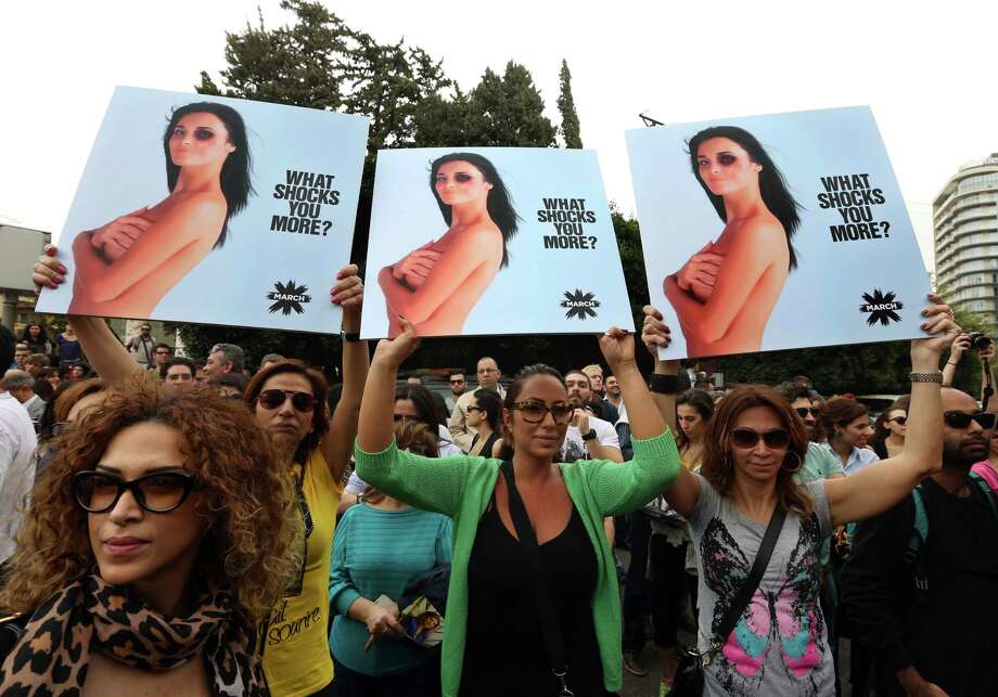 Lebanese women hold posters to mark International Woman's Day during a rally of thousands demanding that parliament approves a law that protects women from domestic violence, in Beirut, Lebanon, Saturday, March. 8, 2014. Although Lebanon appears very progressive on women rights compared to other countries in the Middle East, domestic violence remains an unspoken problem and the nation's parliament has yet to vote on a bill protecting women's rights nearly three years after it was approved by the Cabinet. Photo: Bilal Hussein, AP / AP