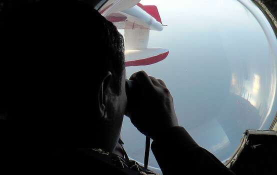 This handout photo taken on March 9, 2014 and released by the Malaysian Maritime Enforcement agency shows Malaysian Maritime Enforcement personnel looking through binoculars during search and rescue operations for the missing Malaysia Airlines (MAS) Boeing 777-200 as they fly over the waters off the northeastern coast of peninsula Malaysia.  Malaysia on March 9 launched a terror probe into the disappearance the day before of the MAS passenger jet, carrying 239 people, investigating suspect passengers who boarded with stolen passports, as relatives begged for news of their loved ones. Photo: Malaysian Maritime Enforcement, AFP/Getty Images