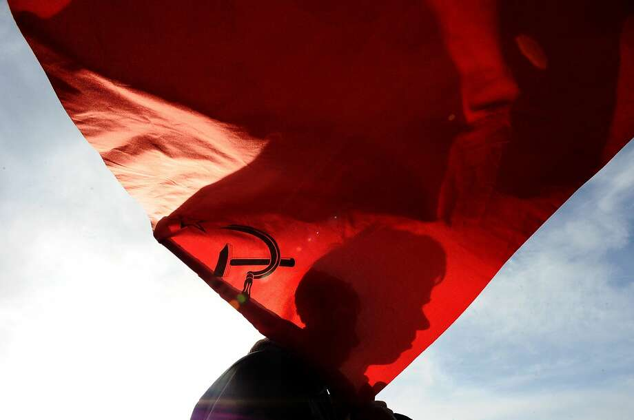 """The silhouette of a mans face is seen on a Soviet Union flag during a rally to show support for pro-Russian authorities in the Ukrainian region of Crimea in St. Petersburg on March 9, 2014. Russia's incursion in Crimea is a """"serious miscalculation"""" and Moscow could face far-reaching economic consequences unless a diplomatic solution can be found, British Foreign Secretary William Hague said on March 9. Photo: Olga Maltsevaolga, AFP/Getty Images"""