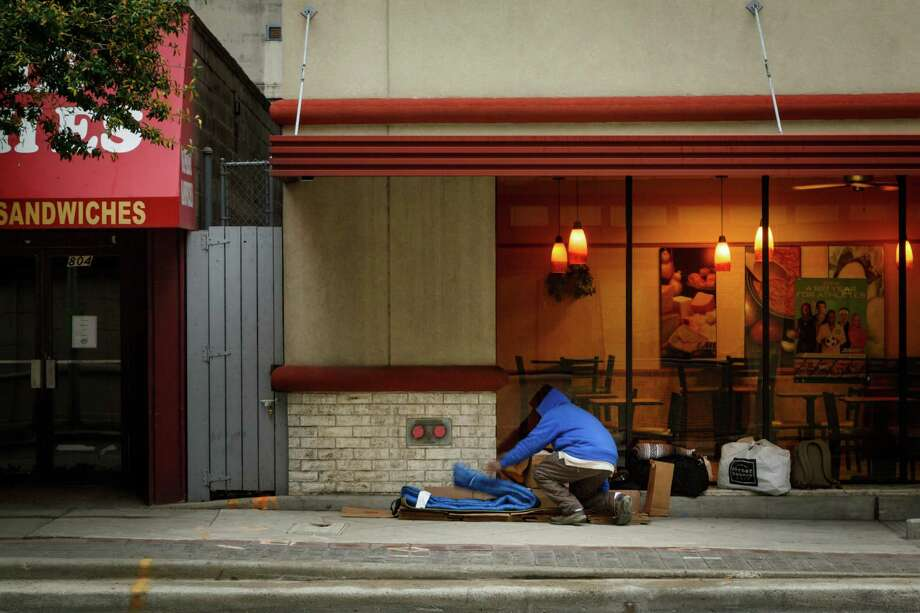 A homeless man, who wished not to be identified, folds up his sleeping bag outside a Subway near Rusk and Miliam Streets on a wintery cold day, Tuesday, Jan. 28, 2014, in Houston. ( Michael Paulsen / Houston Chronicle ) Photo: Michael Paulsen, Staff / © 2014 Houston Chronicle
