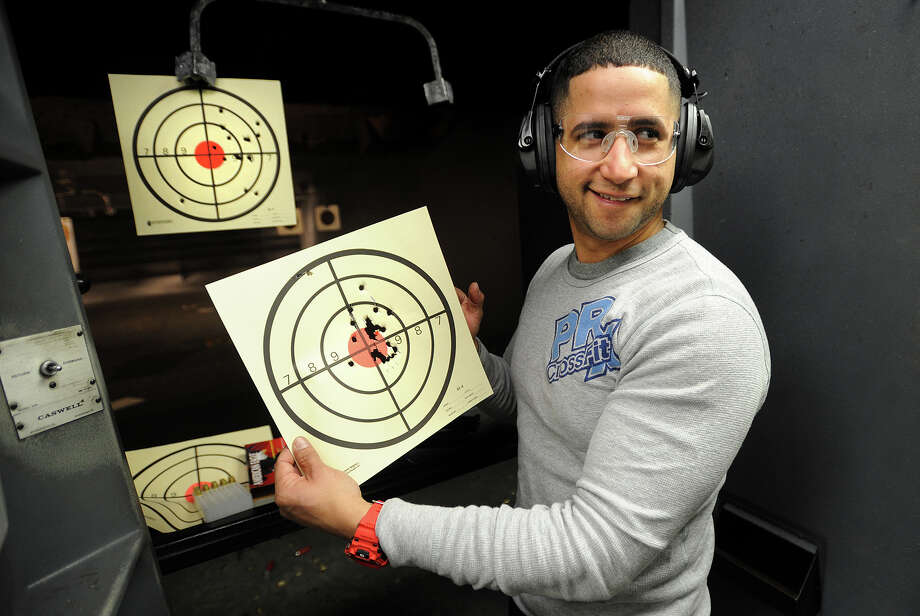 Waterbury police officer Willis Gonzalez, of Milford, shows off his target during an afternoon of shooting with his 40 caliber Smith and Wesson pistol at the Bridgeport Shooting Range in Bridgeport, Conn. on Sunday, March 9, 2014. Photo: Brian A. Pounds / Connecticut Post