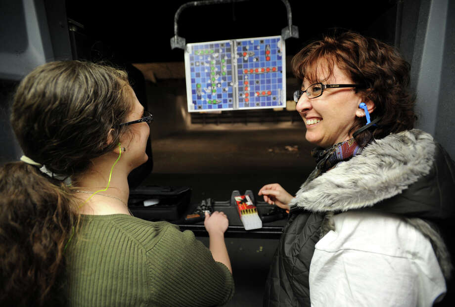 Robyn Ventriglio, left, and her mom Becky, of Shelton, shoot colorful patterned targets with 38 caliber revolvers at the Bridgeport Shooting Range in Bridgeport, Conn. on Sunday, March 9, 2014. Photo: Brian A. Pounds / Connecticut Post