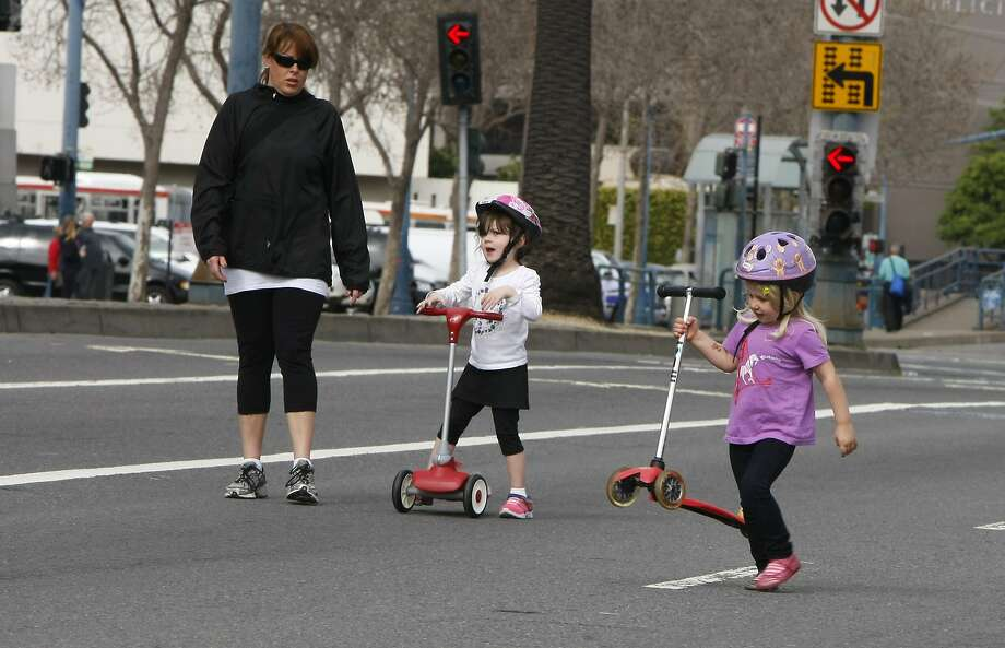 Aimee Dunn guides Makea Gross, 3 (center), and Emma Sanders, 5, on their scooters during the first Sunday Streets of the year, held on the Embarcadero. Photo: Codi Mills, The Chronicle