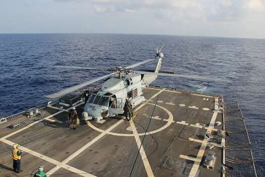 A U.S. Navy helicopter lands aboard Destroyer USS Pinckney during a crew swap before returning to a search and rescue mission for the missing Malaysian airlines flight MH370 in the Gulf of Thailand, Sunday, March 9, 2014. The plane, which was carrying 239 people, lost contact with ground controllers somewhere between Malaysia and Vietnam after leaving Kuala Lumpur early Saturday morning for Beijing. Photo: Chris D. Boardman, Associated Press