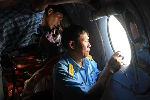 This picture taken from aboard a flying Soviet-made AN-26 used as a search aircraft by Vietnamese Air Force to look for missing Malaysia Airlines flight MH370, shows an officer (R) and a reporter looking out the window during search operations over the southern seas off Vietnam on March 9, 2014. Malaysia on March 9 launched a terror probe into the disappearance of a Malaysian Airlines passenger jet carrying 239 people the day before, investigating suspect passengers who boarded with stolen passports, as relatives begged for news of their loved ones. The United States sent the FBI to investigate after Malaysia Airlines flight MH370 vanished from radar early on March 8 somewhere at sea between Malaysia and Vietnam, but stressed there was no evidence of terrorism yet. Photo: Hoang Dinh Nam, AFP/Getty Images