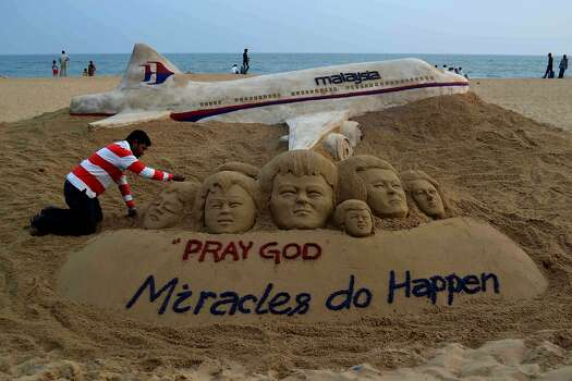 Indian sand artist Sudersan Pattnaik gives final touches on a sand sculpture with a message of prayers for the missing Malaysian Airlines flight MH370 - which vanished from radar early on March 8 somewhere at sea between Malaysia and Vietnam - at Puri beach, some 65 kilometers away from Bhubaneswar, on March 9, 2014. Malaysia on March 9 said a missing airliner carrying 239 people may have inexplicably turned back, as authorities launched a terror probe into the plane's sudden disappearance, investigating suspect passengers who boarded with stolen passports. Photo: Asit Kumar, AFP/Getty Images