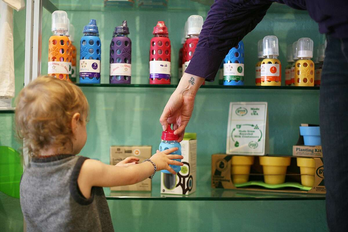Heather Rider hands her son Colin a glass bottle for him to drink out of at her store, Monkey Bars, in Alameda, Calif. on Thursday, March 6, 2014. New research shows that items with low doses of BPA are more safe than BPA-free items.