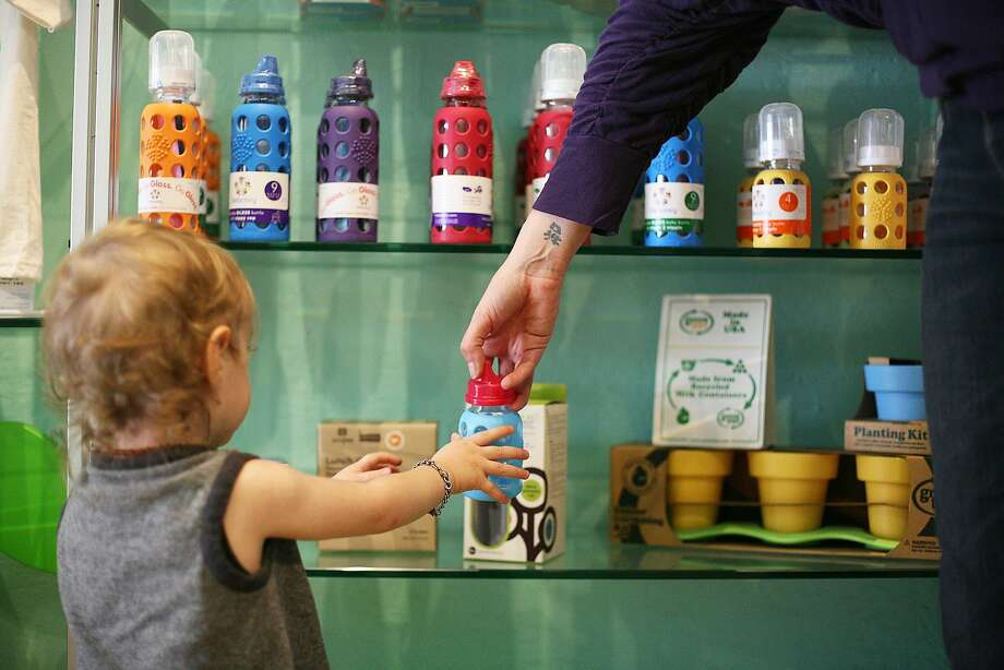 Heather Rider hands son Colin a glass bottle at her eco-friendly store, Monkey Bars. Photo: James Tensuan, Special To The Chronicle