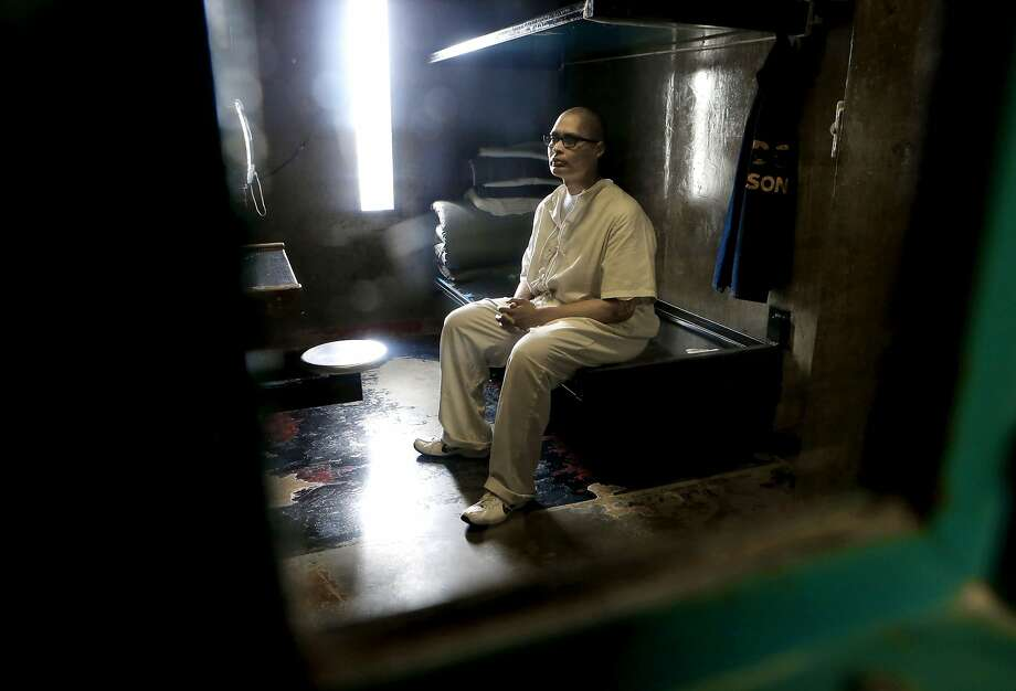 Anthony Torres, serving a life sentence for murder, sits inside his Security Housing cell. At 48, he's studying for his high school equivalency certificate, and a teacher gives him tests from outside his cell door. Photo: Michael Macor, The Chronicle