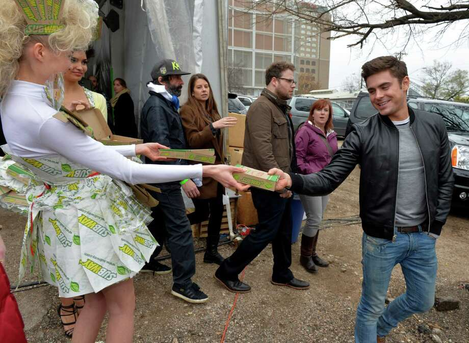 IMAGE DISTRIBUTED FOR SUBWAY RESTAURANTS - A SUBWAY model hands Zac Efron the brand's new Flatizza product following a Tumblr Q&A event at SXSUBWAY square in Austin, Texason Sunday, March 9, 2014. (Photo by Jack Dempsey/Invision for SUBWAY Restaurants/AP Images) Photo: Jack Dempsey, Getty Images / Invision