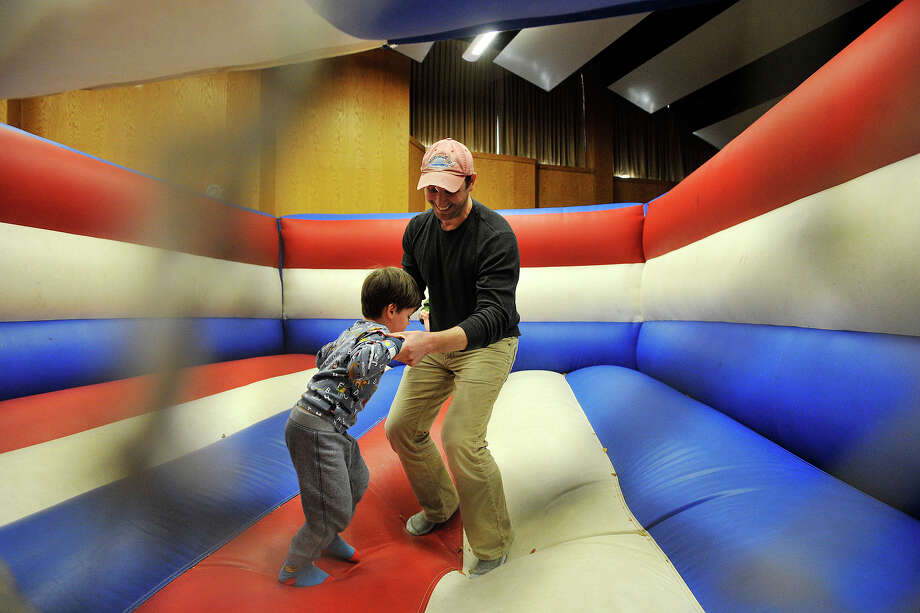 Daniel Katz jumps around an inflated bouncy room with his son, Oliver, during the 22nd annual JCC Purim Carnival: Under the Big Top at the Jewish Community Center in Stamford, Conn., on Sunday, March 9, 2014. Photo: Jason Rearick / Stamford Advocate
