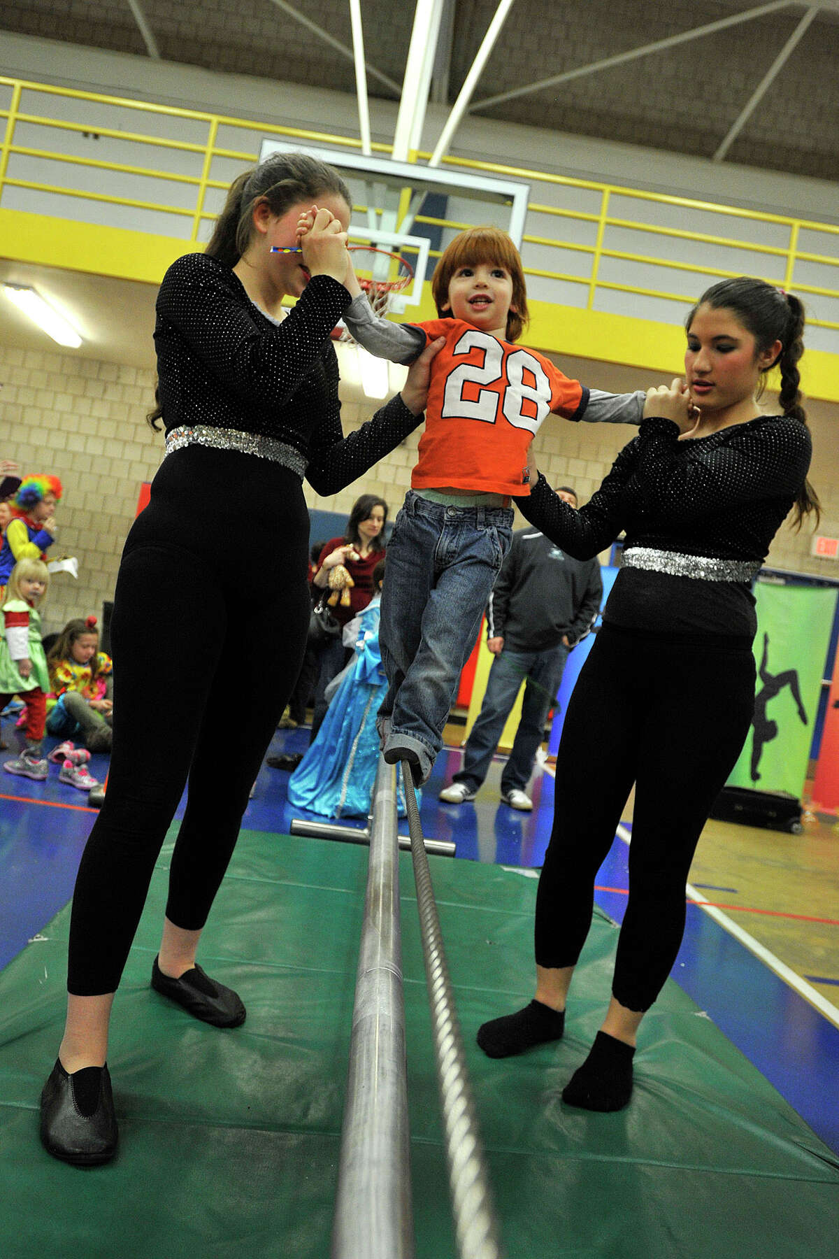 Luke Vartuli is led across the tightrope by Sophia Greenberg, left, and Danielle Blau during the 22nd annual JCC Purim Carnival: Under the Big Top at the Jewish Community Center in Stamford, Conn., on Sunday, March 9, 2014.