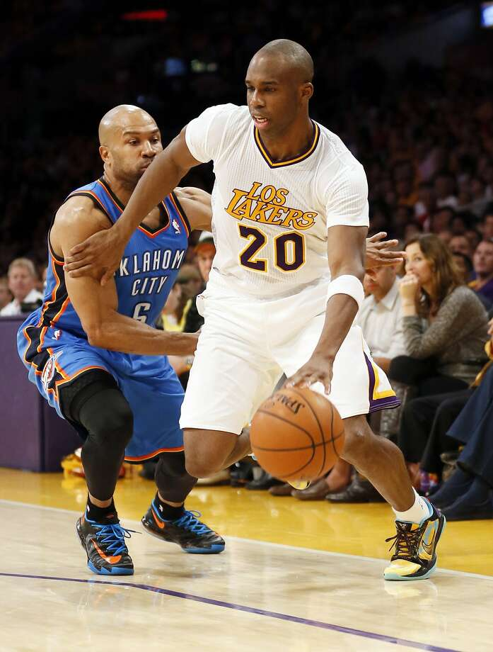 Jodie Meeks drives around a former Lakers guard, Derek Fisher, during a 42-point performance that lifted Los Angeles to a stunning victory. Photo: Danny Moloshok, Associated Press