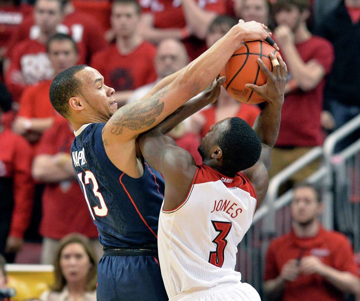 Connecticut's Shabazz Napier, left, blocks the shot of Louisville's Chris Jones during the first half of an NCAA college basketball game, Saturday, March 8, 2014, in Louisville, Ky.
