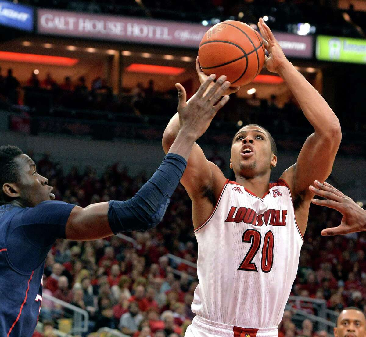Louisville's Wayne Blackshear shoots as Connecticut's Amida Brimah defends during the second half of an NCAA college basketball game, Saturday, March 8, 2014, in Louisville, Ky. Louisville defeated UConn 81-48.