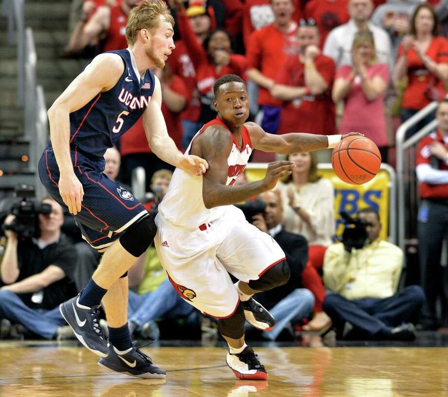Louisville's Terry Rozier, right, drives around the defense of Connecticut's Niels Giffey during the second half of an NCAA college basketball game, Saturday, March 8, 2014, in Louisville, Ky. Louisville defeated UConn 81-48. Photo: Timothy D. Easley, AP / Associated Press