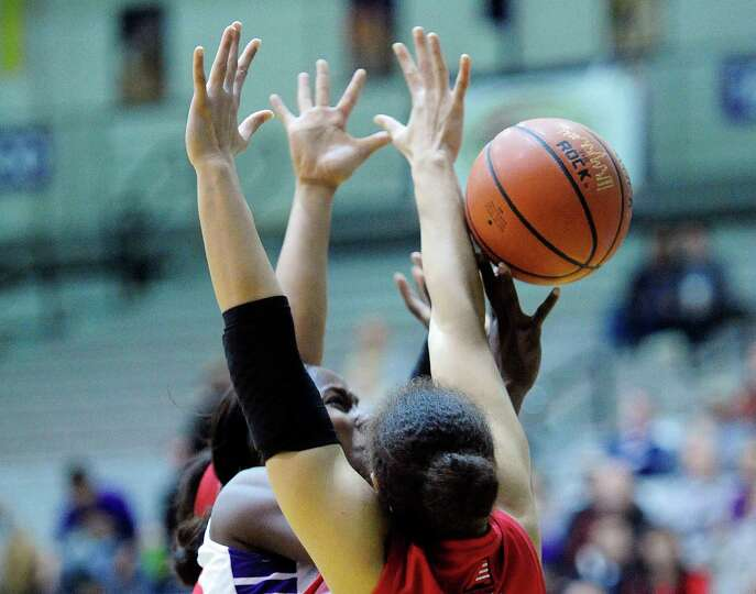 UAlbany's Shereesha Richards, center, drives to the basket between two Hartford players during their