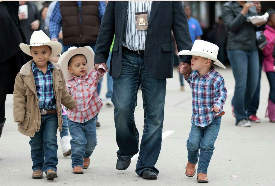 Larry Parker walks a group of young cowboys through the crowds, at left, Terence Sherbrook, 5, Zane Parker, 2, and Brayden Parker, 4, at the Houston Livestock Show and Rodeo at Reliant Stadium Sunday, March 9, 2014, in Houston. Photo: Johnny Hanson, Houston Chronicle / © 2014  Houston Chronicle