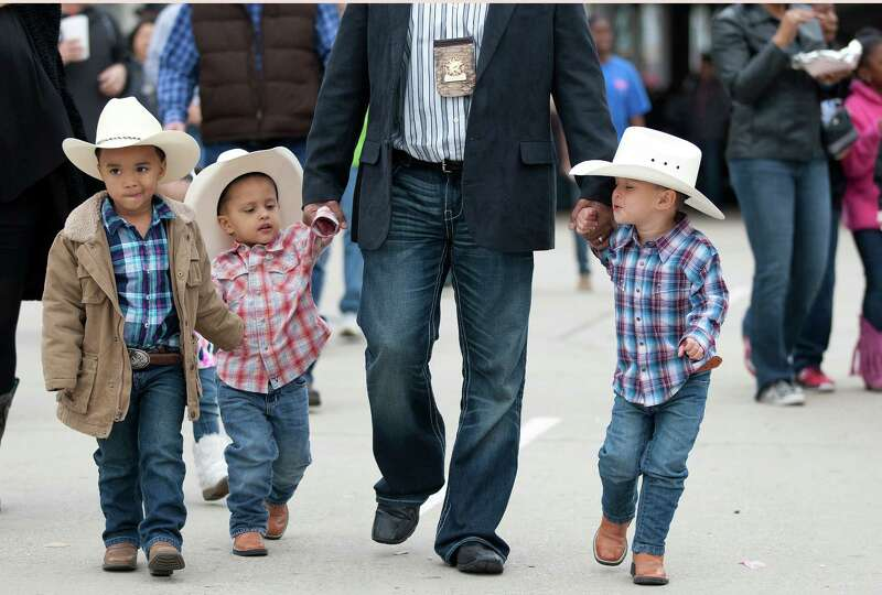 Larry Parker walks a group of young cowboys through the crowds, at left, Terence Sherbrook, 5, Zane