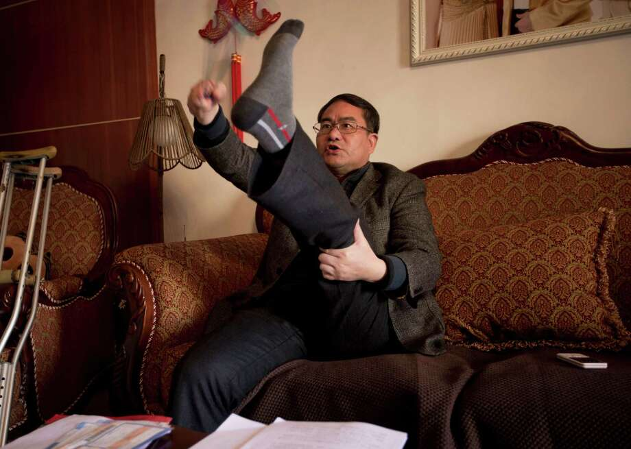 Zhou Wangyan, head of the Liling city land resources bureau in China, demonstrates how he was tortured by Communist Party anti-graft investigators. Photo: Andy Wong, STF / AP