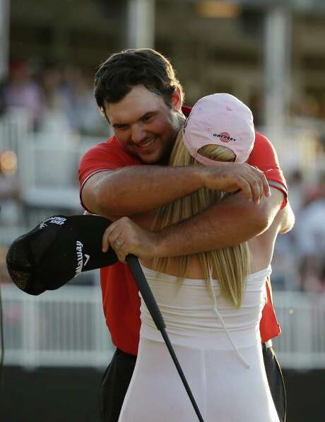 Hugging his wife Justine after winning is becoming a habit for Patrick Reed, who won for the third time in seven months. Photo: Lynne Sladky, STF / AP