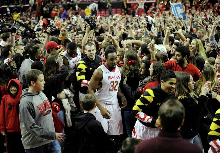 Maryland's Dez Wells (32) and others make their way through the mob after Maryland fans rushed the floor after beating Virginia 75-69 in overtime of an NCAA college basketball game, Sunday, March 9, 2014, in College Park, Md. (AP Photo/Nick Wass) ORG XMIT: CPX109 Photo: Nick Wass / FR67404 AP
