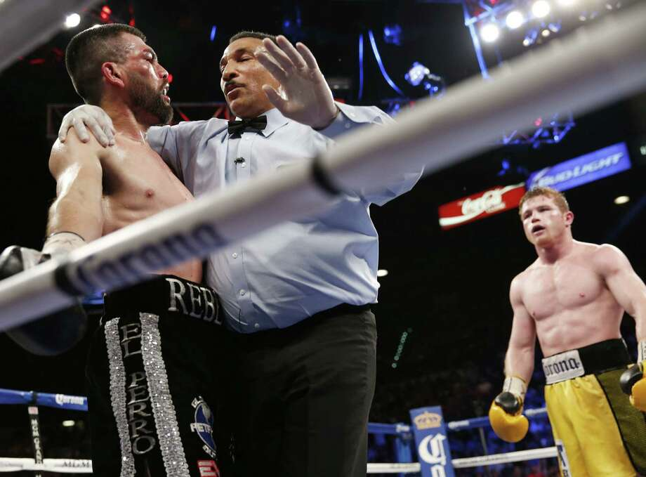 "Referee Tony Weeks steps between Alfredo Angulo (left) and Saul ""Canelo"" Alvarez in stopping the fight in the 10th round. Photo: Eric Jamison / Associated Press / FR156391 AP"