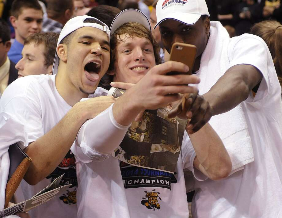 The Shockers' Fred VanVleet (from left), Ron Baker and Cleanthony Early mark the moment with a photo. Photo: Bill Boyce, Associated Press