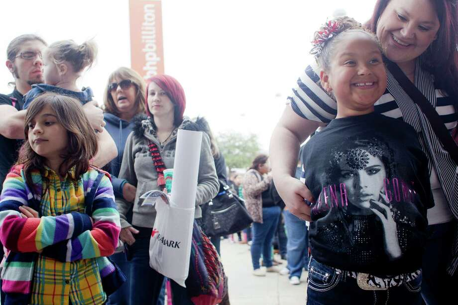 Kaci Parrack, 8, at right, is hugged by her mother, Leah, as the two were first in line Sunday for the Selena Gomez concert at RodeoHouston. Gomez, a Grand Prairie native, played an hourlong set before a packed house at Reliant Stadium. Photo: Johnny Hanson, Staff / © 2014  Houston Chronicle