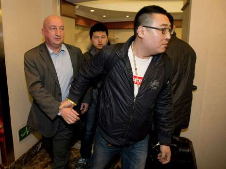 Hugh Dunleavy, left, from commercial director of the Malaysia Airlines is escorted by an unidentified Chinese man after speaking for relatives or friends of passengers aboard the missing plane, in Beijing Sunday, March 9, 2014.  Photo: Andy Wong, STF / AP