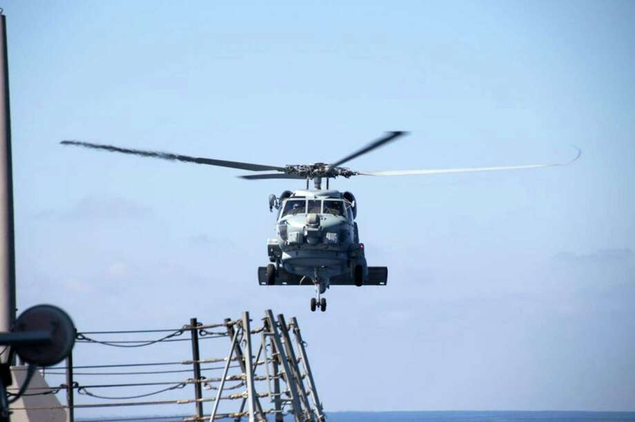 A U.S. Navy helicopter takes off from the USS Pinckney to help search for the Malaysian Airlines jetliner. Photo: Uncredited, HOPD / Navy Media Content Service