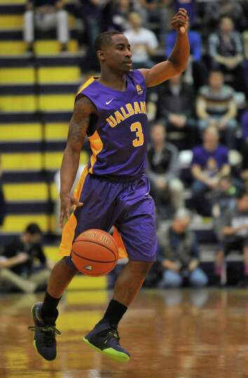 UAlbany's DJ Evans (3) moves the ball against Vermont during the first half of the America East Tour