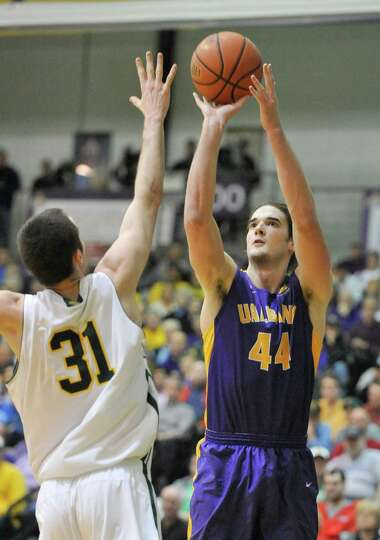 UAlbany's John Puk (44) is defended by Vermont's Clancy Rugg (31) during the first half of the Ameri