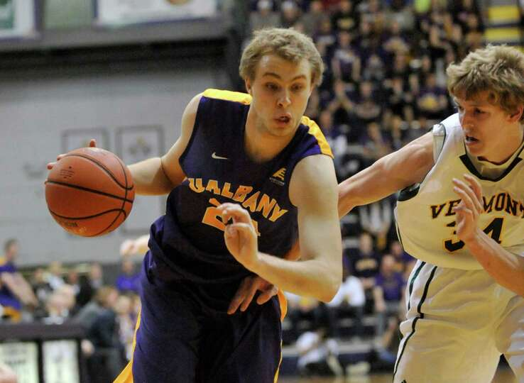 UAlbany's  Dallas Ennema (24) is defended by Vermont's Kurt Steidl (34) during the first half of the