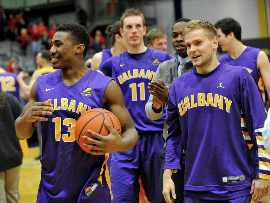 UAlbany players celebrate a 67-58 win over Vermont during America East Tournament semifinal Men's basketball game in Albany, N.Y., Sunday, March 9, 2014.(Hans Pennink / Special to the Times Union) ORG XMIT: HP111 Photo: Hans Pennink / 00025987A