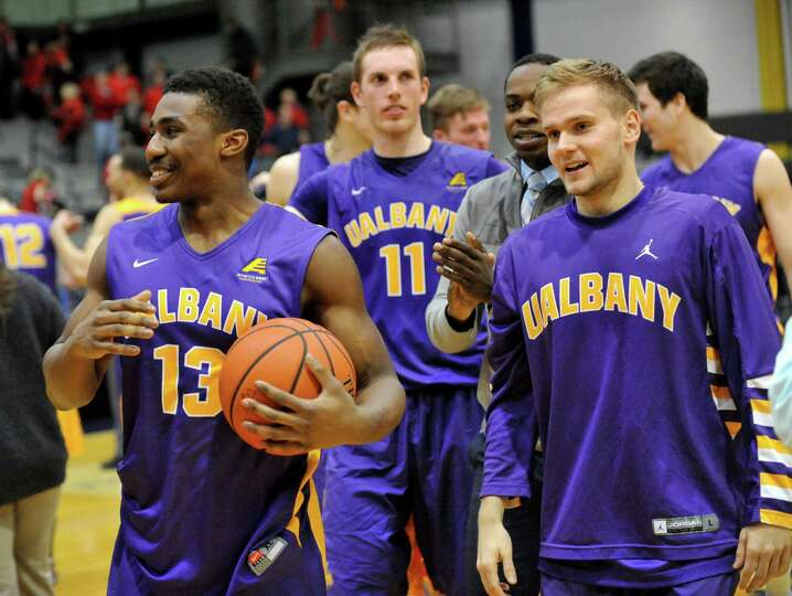UAlbany players celebrate a 67-58 win over Vermont during America East Tournament semifinal Men's ba