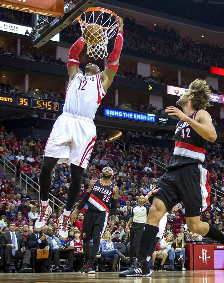 Rockets center Dwight Howard dunks the ball past Trail Blazers center Robin Lopez. Photo: Smiley N. Pool, Houston Chronicle