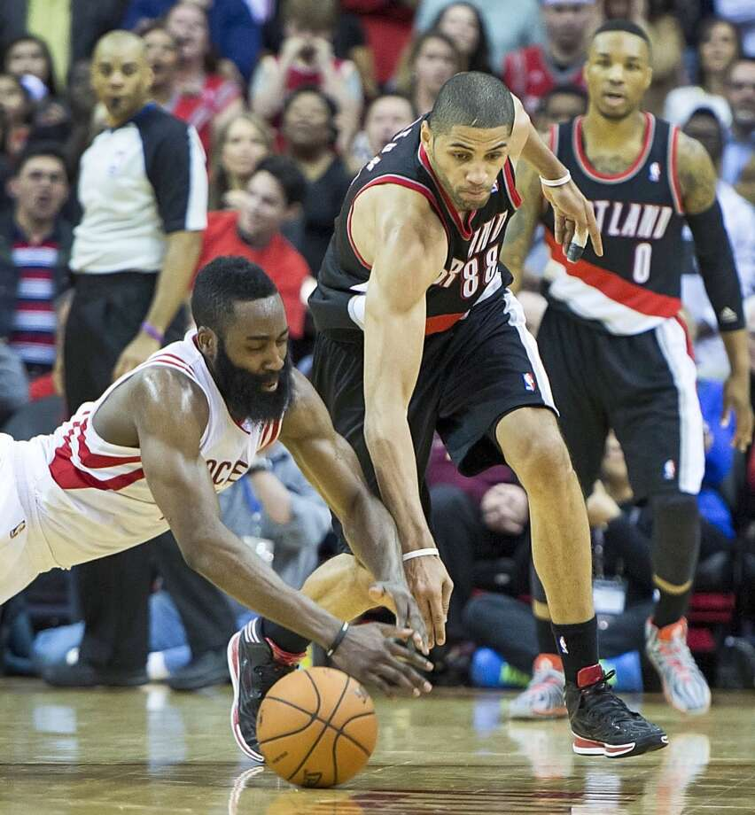 Rockets guard James Harden fights Trail Blazers forward Nicolas Batum for a loose ball. Photo: Smiley N. Pool, Houston Chronicle