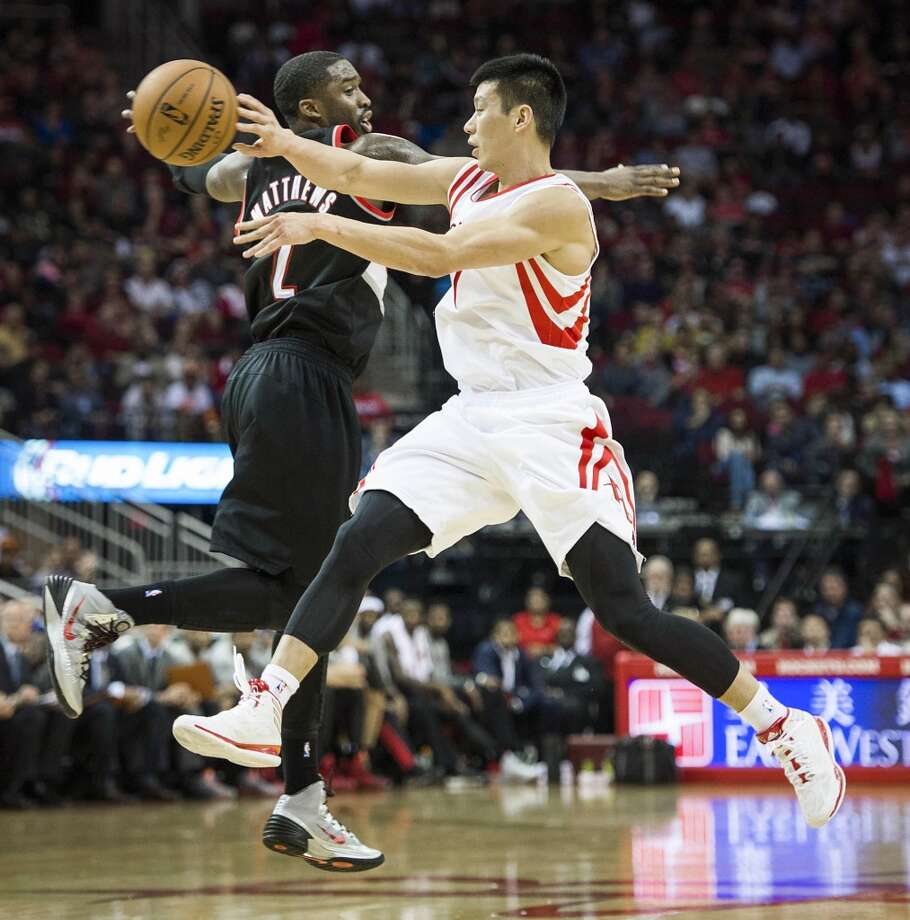 Rockets point guard Jeremy Lin passes the ball around Trail Blazers shooting guard Wesley Matthews. Photo: Smiley N. Pool, Houston Chronicle
