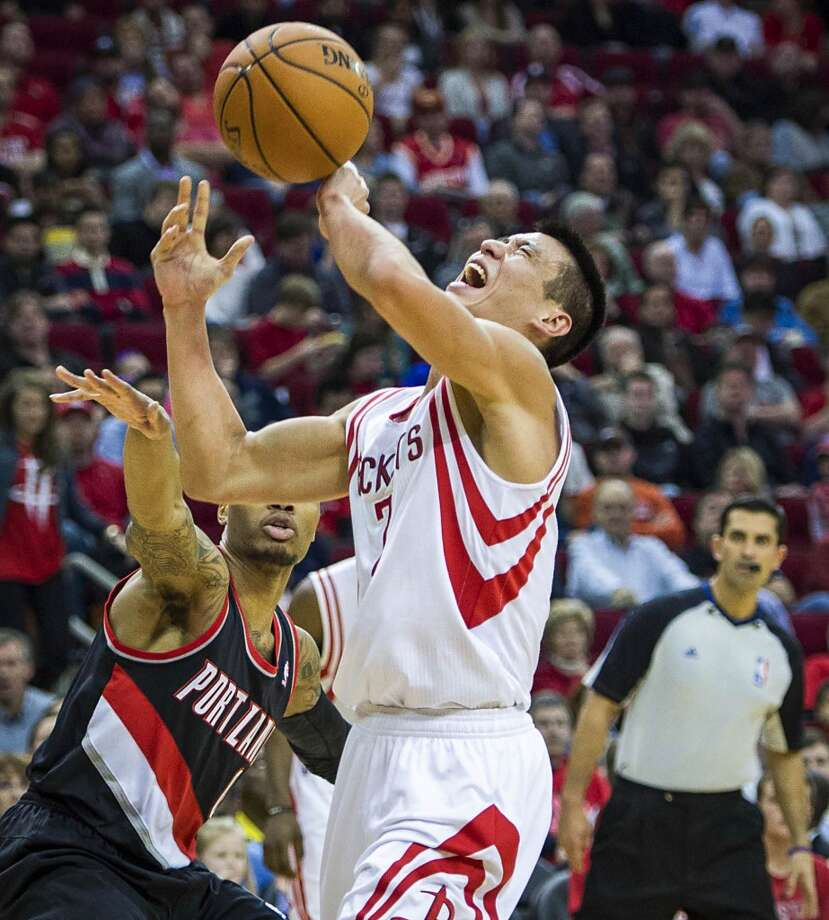 Rockets point guard Jeremy Lin has the ball knocked away by Trail Blazers point guard Damian Lillard. Photo: Smiley N. Pool, Houston Chronicle