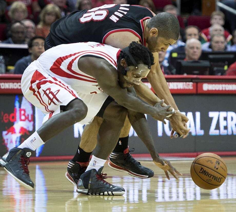 Rockets point guard Patrick Beverley fights for a loose ball against Trail Blazers small forward Nicolas Batum. Photo: Smiley N. Pool, Houston Chronicle